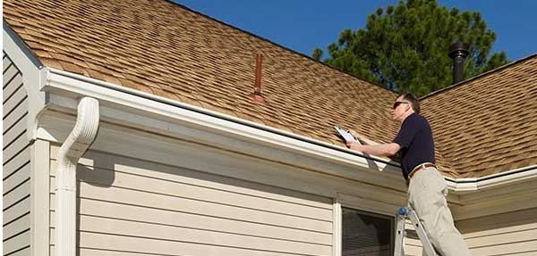 Image of a man inspecting a roof.
